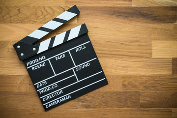 Cinema clapperboard on wooden background - Movie entertainment concept