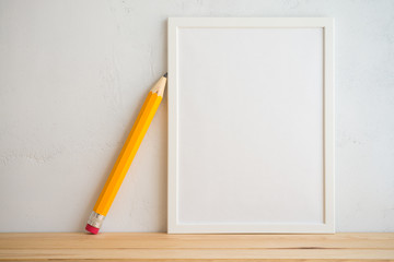 Photo frame and pencil on white wall background, creative ideas back to school concept