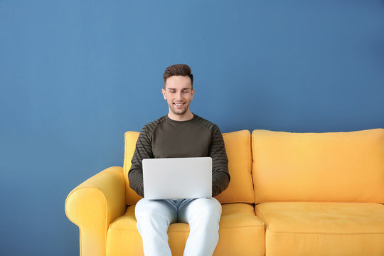 Handsome young man with laptop sitting on sofa, indoors