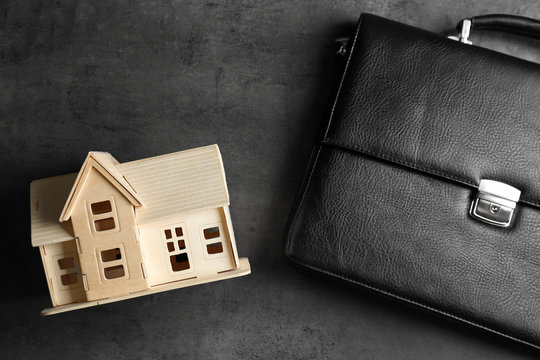 Briefcase and model of house on grey background. Concept of balance between work and personal life