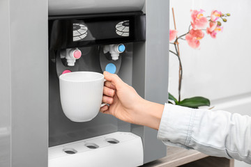 Woman filling cup from water cooler, closeup