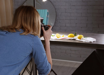 Woman taking photo of food with professional camera in studio