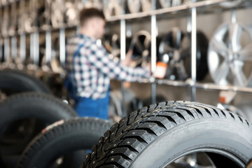 Car tires and blurred male mechanic on background in automobile service center Wall mural