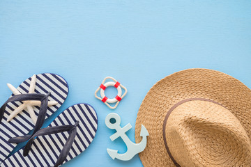 Flat lay of tropical beach summer holiday with beach summer accessories for traveling on blue wooden background