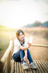 happy young asian woman taking selfie form smartphone during summer Sunset with landscape background