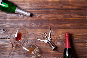 Photo of two bottles of wine, two wine glasses and corkscrew