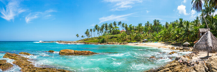 Panoramic view of a small lagoon with traditional wooden fishing boats and old bungalow on the beach in Sri Lanka.