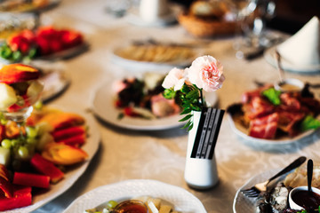 wedding table with delicious dishes and a small vase with roses