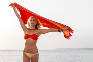 Beautiful woman on the beach holding a scarf. Soft focus