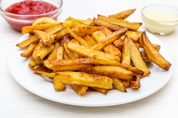 Plate with french fries and saucers with sauces on the white wooden table.