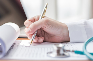 Physician doctor writing on medical health care record, patients discharge, or prescription form paperwork in hospital clinic