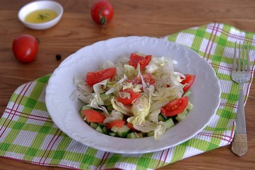 Vegetable salad with tomatoes, cucumber and lettuce dressed with olive oil