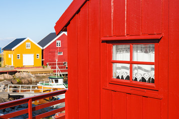 Wall Mural - Red boathouse with a fishing boat at the harbor