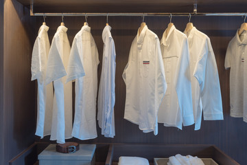 row of white shirts on rail in wooden closet
