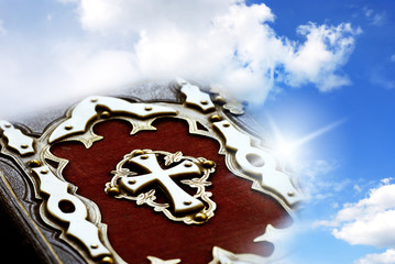 Wall Mural - Christian Catholic bible with cross over cloudy sky