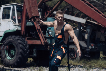 Man, builder or bodybuilder with strict face in overalls