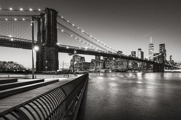Fotomurales - Brooklyn Bridge Park boardwalk in evening with the skyscrapers of Lower Manhattan, East River, and the Brooklyn Bridge in Black & White. Brooklyn, New York City