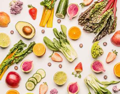 Colorful fruits and vegetables flat lay background with half of oranges,avocado, citrus,apples and berries , top view. Healthy food and clean eating ingredients concept