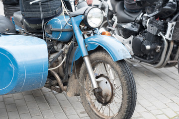 vintage motorcycle with sidecar parked near modern bikes