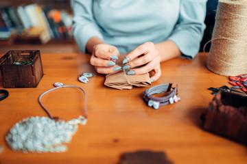 Female master with scissors makes handmade earring