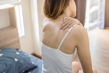 Woman suffering from neck pain on the bed