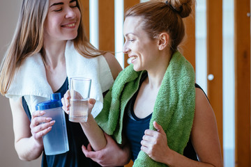 Two sporty yogi women in fitness studio clinking glasses, taking a break and drinking water. Close up portrait