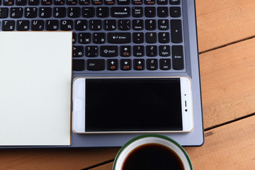 A laptop and a cup of coffee on a wooden background, a workstation on an old desk, a smartphone and a notebook, a pen and glasses in the workplace, a copy of space, a designer workstation