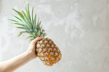 Female hand holding a pineapple on grey background