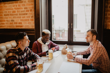 Multiracial friends talking and drinking beer and clinking glasses at pub