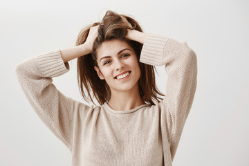 Girl feels like she need to visit hairdresser. Portrait of carefree attractive female with broad smile lifting hair up with hands, and tilting, being home and making bun to prepare dinner