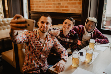 Happy male friends taking selfie and drinking beer at bar or pub