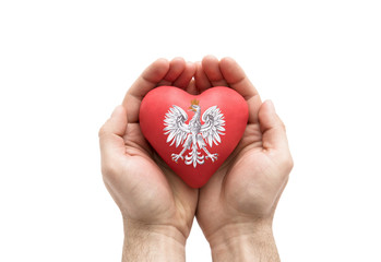 Hands covering Polish coat of arms on a red heart isolated on white background. Clipping path included.