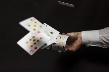 Flying playing cards with hand on a dark background