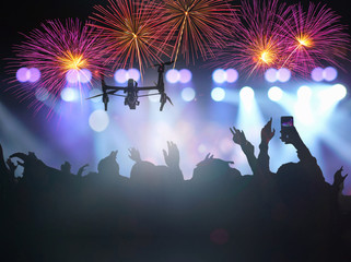 Closeup silhouette of Drone flying for taking video of Concert crowd with multiclors fireworks in silhouettes of Music fanclub with show hand action which follow up the songer with follow light