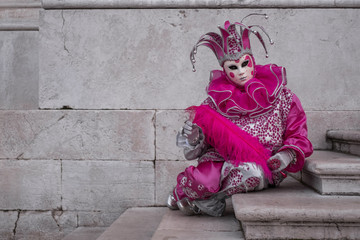 Woman dressed up as jester in pink costume at the Venice Carnival (Carnivale di Venezia) Wall mural