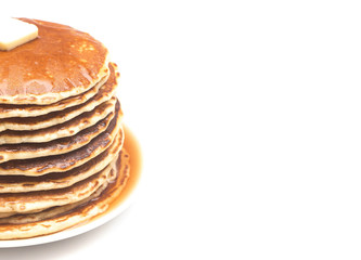 A Stack of Fresh Buttermilk Pancakes with Butter and Syrup on a White Background
