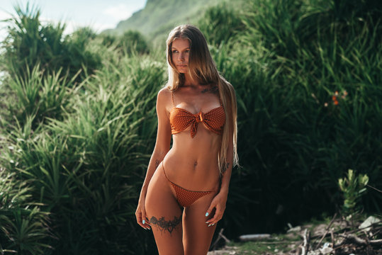 Delicate blond girl with perfect elegant body and tattoo on her leg and breast posing in red swimsuit at the beach with tropical green trees at background. Attractive Woman with long hair outdoors