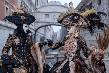 Venice Carnival: Two woman in costumes and masks, carrying feathered bird and birdcage
