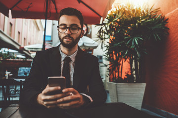 Serious businessman with the beard and formal suit, in the glasses, is sitting alone in an outdoor cafe next to his office and waiting for his lunch while using the smartphone to talk with colleagues