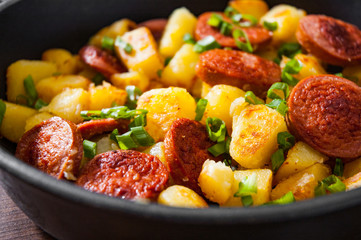 Roasted Potato and Sausage in frying pan on wooden table