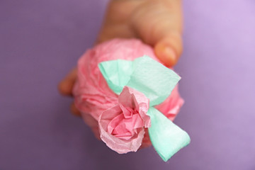 Easter egg in a child's hand. Selective focus. baby find the egg. The egg is wrapped in gift pink paper with mint green ribbon and flower. purple felt background. Creative concept of Easter