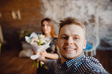 Selfie man gives a gift bouquet of flowers to a young woman. couple