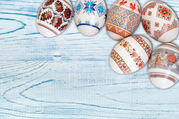 Happy Easter card. Colorful shiny easter eggs on blue wooden table background. Copy space for text.