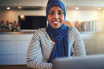 Smiling Arabic female entrepreneur using a laptop in her kitchen