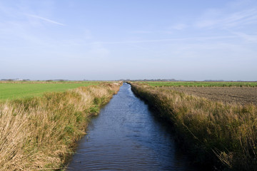 "Foehr / Germany: The small ""Borsumer Arm"" channel for the drainage of the marsh fields near Oldsum on the Frisian island in autumn"