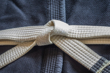 White belt of Brazilian Jiu-Jitsu with four degrees, tied in the kimono, knot of belt.