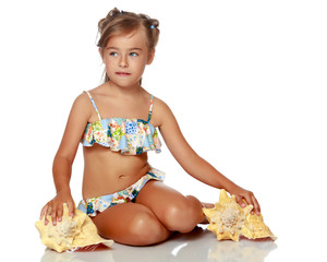 Little girl in a swimsuit with a seashell