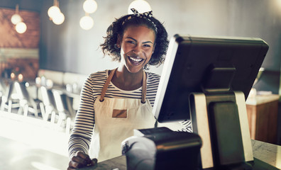 African waitress laughing while working in a trendy restaurant