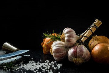 A bunch of garlic, an onion, salt and spices on a black slate