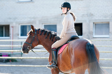 Young lady riding a horseback at equestrian farm